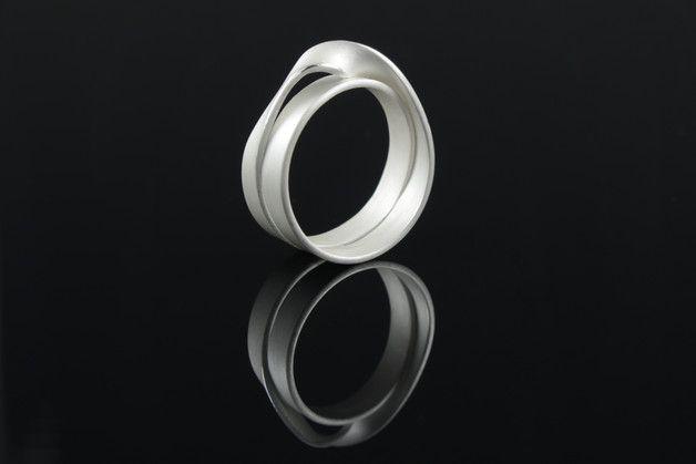 **Das Schmuckstück**  Gummiband oder Silber? Dieser spannend gekordelte Silberring hat die Optik eines gedrehten Gummibandes. Ob als Schmuckring, Ehering oder Freundschaftsring, dieser Ring wird...