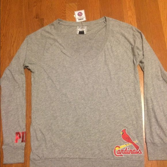 Victoria Secret Pink St. Louis Cardinals Shirt Super cute gray long sleeved Tshirt from Victoria Secret. The shirt still has the tags on it. There is a team logo on the lower left and on the right sleeve the word pink is written in red.  The back of the shirt says caught looking. PINK Victoria's Secret Tops Tees - Long Sleeve