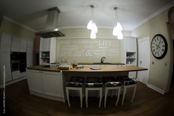 In the kitchen: the owners' artistic style was emphasized by a personalized art wall; Andreea Radu, the painter made a collection of static nature inspired by the textiles from the kitchen, the written wall represents  the mother's messages to the fanily members, the different letters representing the name of each member of the family.