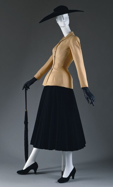 "1947 Dior suit iconic of the ""New Look"" that would carry into the 50's.  Padded hips, articulated bustline and nipped waist.  Unlike the similar silhouette of the mid nineteenth century, the figure was expected to fit this silhouette through internal methods, ie dieting, rather than restrictive corsets.  Brassiere's and elastic girdles were worn instead.  Even waist cinchers of the 50's were only 4 inches wide."
