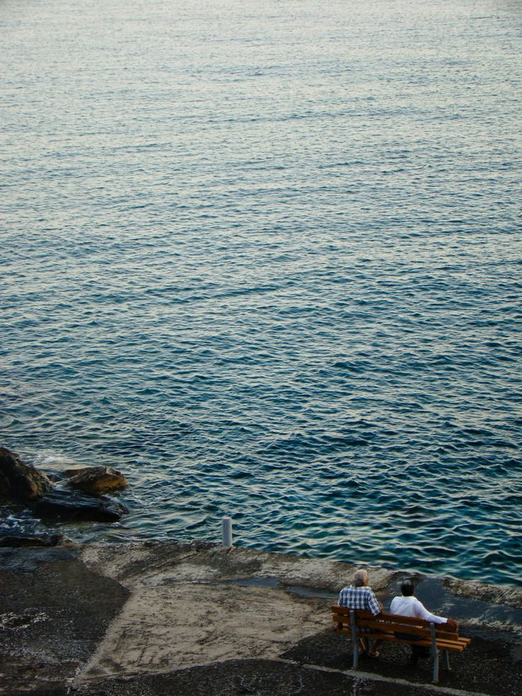 Friends. Looking at the sea. Isternia bay - Tinos Island. Greece.
