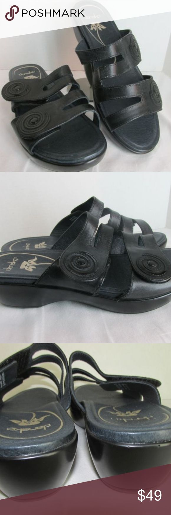 """Dansko Black Leather Dixie Sandals Wedges 40 9.5 Black leather uppers, padded insoles. Platform front with wedge heel. Strappy double upper with patent swirl flower detail, adjustable hook/loop tape close. Size 40 (9.5-10 US)   Length (insole tip of toe to back edge of heel cup) 9.75"""" Width (outersole at widest/ball) 3.5"""" Platform 1"""" Heel height 2""""  Excellent previously owned. Dansko Shoes Sandals"""
