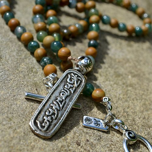 """OurPrayerNecklace has been designed with Moss Agate and wood-laced Gemstones,carrying the hand-carved Mantra """"Om Mani Padme Hum"""" amulet. 108 prayer gemstone beads to invoke the sacred power of this mantra. Promoting strength and inspiration for new beginnings. Feel grounded and focused, these Gemstones will aid you with concentration and persistence to clear obstacles, and allow you to see all that is possible.  Length of the Necklace is ..."""