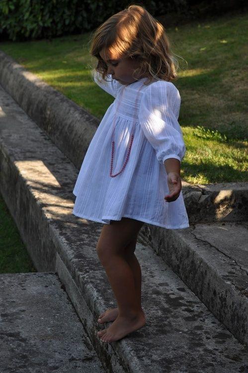 adorable girl in a boho white dress