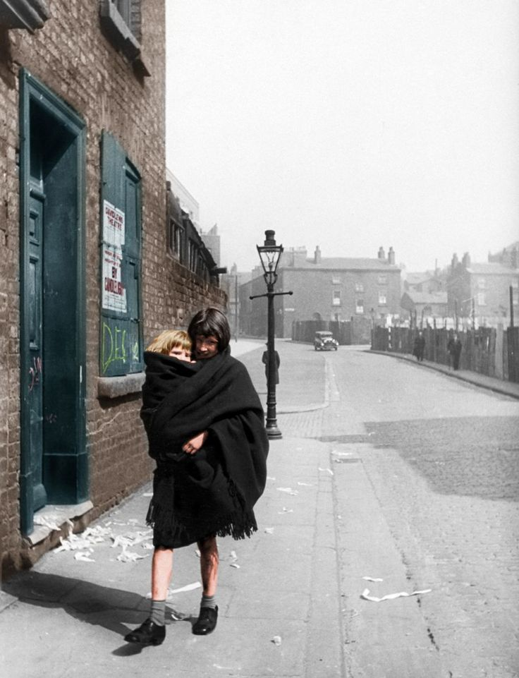 Colour version of picture. Young mother carries her child in a shawl, Liverpool. 3rd April 1939