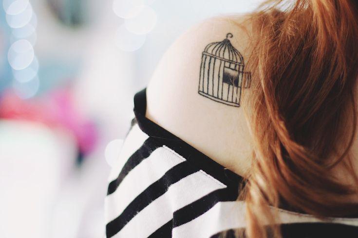 Tatuagem de gaiola aberta no ombro direito.