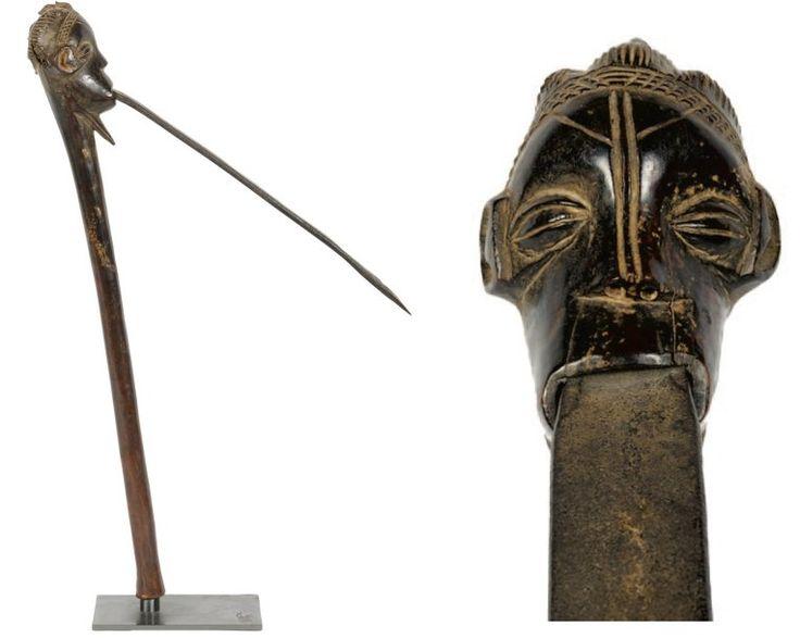 HERMINETTE. Le manche en bois sculpté surmonté d'une tête humaine qui