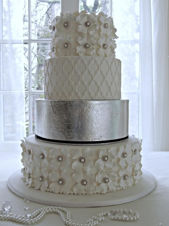 Silver Leaf Wedding Cake ~  		Pearlize gumpaste dogwood flowers with dragee broaches on the top and bottom tiers.  Marvelous Mold overlay on the second tier and edible silver leaf on the third ~ all edible