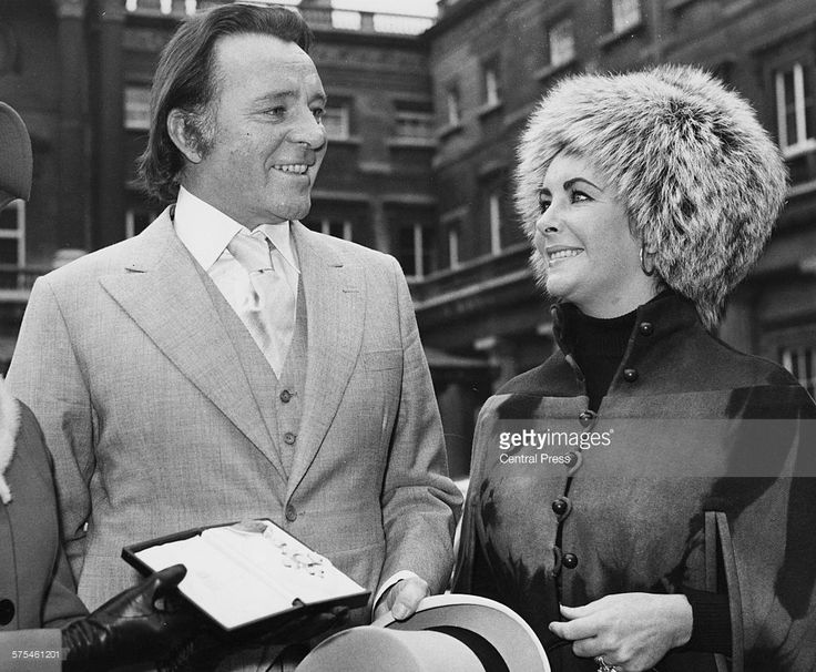 Actors and spouses Richard Burton, wearing a three piece suit, and Elizabeth Taylor, wearing a fur hat, pictured after he received his investiture from Buckingham Palace, London, November 10th 1970.