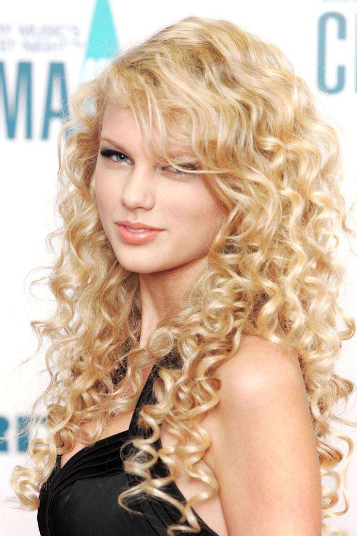 A young Taylor Swift in tight tendrils at the 40th Annual CMA Awards.   - HarpersBAZAAR.com