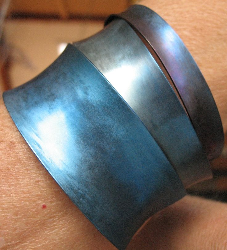 Heidi Janssen. Set geslagen armbanden van titanium. een mooie, karakteristieke set armbanden van titanium met een rustieke uitstraling door de slag. Deze armbanden zijn in blauwe tinten van diep donker- tot licht ijsblauw. Ook mogelijk in andere kleuren die het titaniumpalet biedt. Mooi om ze alledrie samen te dragen!