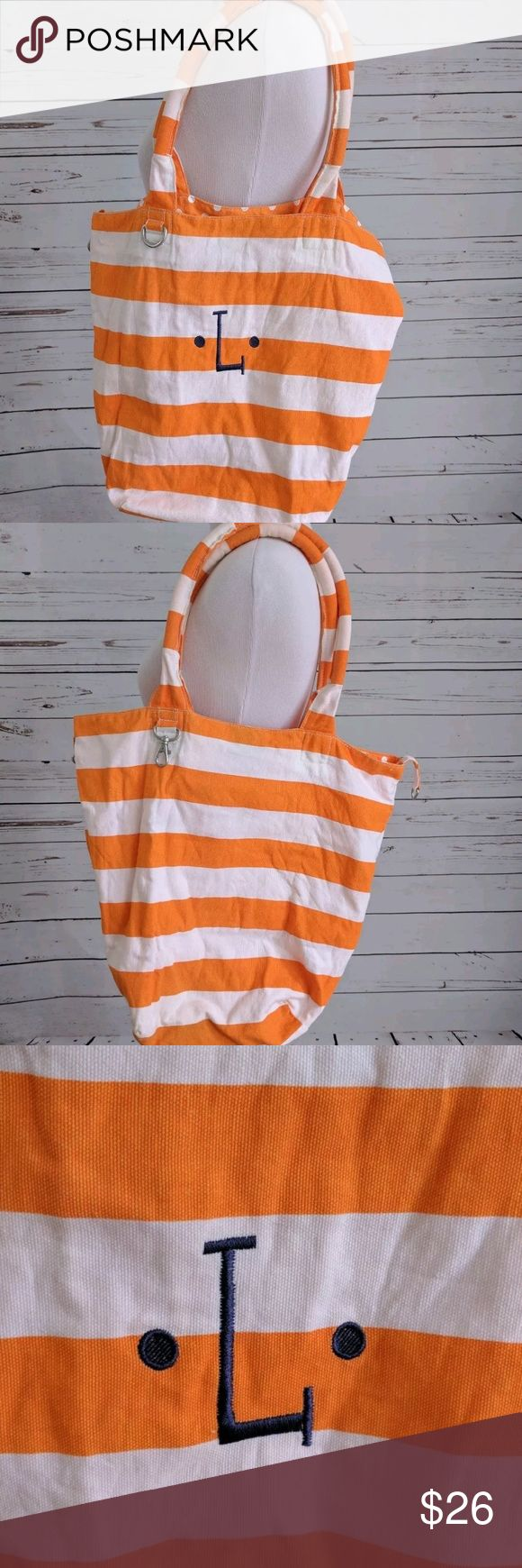 THIRTY-ONE | monogrammed orange tote Orange and white striped Thirty-One canvas tote bag with padded handles. Interior in orange with white polkadots. There is a navy blue L monogrammed on the front. Bag has a square bottom and an inside mesh zippered pocket, zipper functions.   MEASUREMENTS:   Bottom square: 9x9 inches  Depth: 14 inches  handles: 22 inches Thirty-one Bags Totes