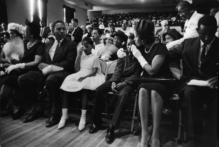 At the funeral for slain Civil Rights leader Medgar Evers, his wife, Myrlie Evers (second right), comforts their son, Darryl Kenyatta Evers, while daughter Reena Denise Evers (center, in white dress) wipes her own tears, Jackson, Mississippi, June 15, 1963.