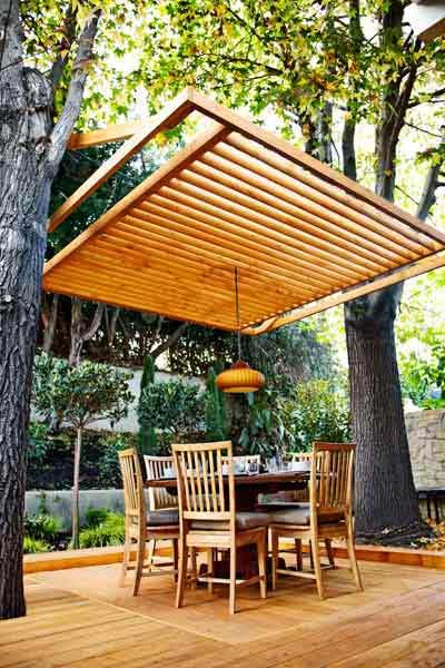 As an alternative to a freestanding pergola, this slatted ceiling covers an open deck, using mature, sturdy tree trunks as supports.