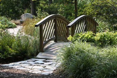 brug over beekje (hoeft niet bol, kan ook vlak) verschillende materialen verharding, loopt slingerend naar een terrasje achter in tuin.