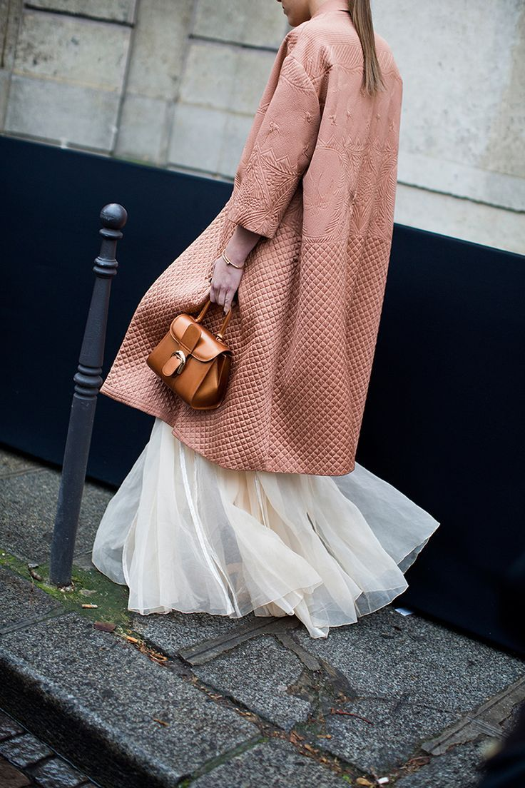 Detailed salmon embellished duster coat thrown over a cream maxi tutu skirt