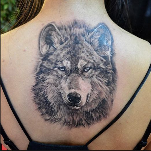 Wolfie here looks like he is about to rock your world. #inked #inkedmag #tattoo #wolf #art #back #arctic #animal #creature