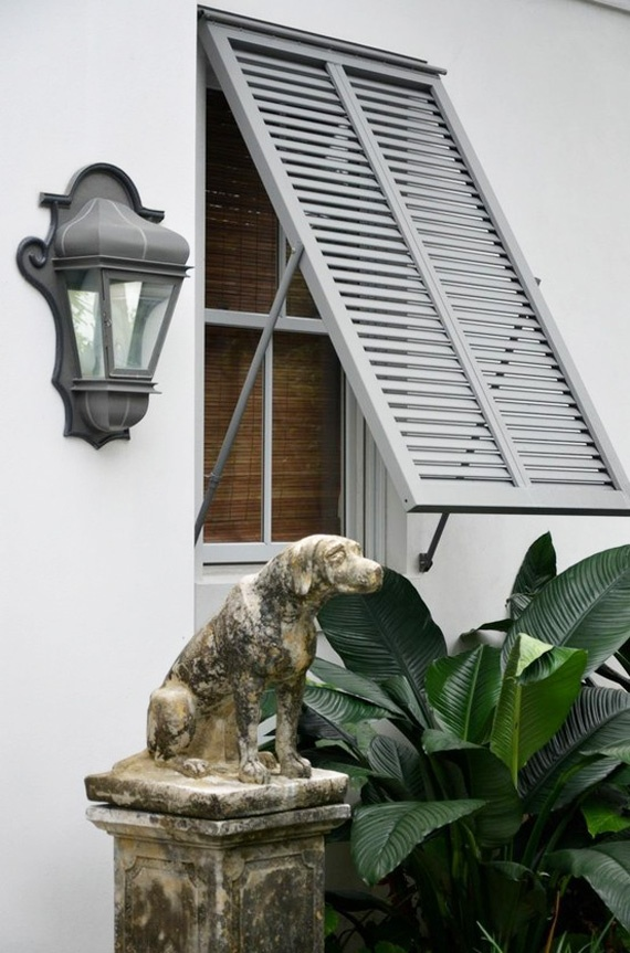 Light grey shutters with the greenery and to top it all off that amazing dog statues