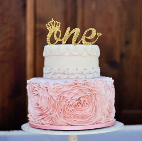 "I'm thinking of having the cake be the bottom layer of this but white. I have a gold glitter ""One"" to add on top. Maybe a real little pink flower or two next to it?"
