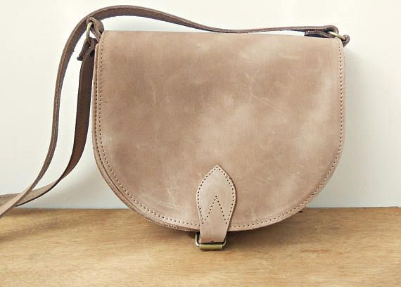 Athena Mocha Saddle bag  Twininas handmade Greek genuine leather equestrian-inspired crossbody bag in mocha (taupe) leather color. Has two pockets and adjustable shoulder carry easily accommodates essentials, this bag will carry you stylishly through the week . Closes with leather strap. DIMENSIONS:  Height: 6.69 inches / 17 cm Width: 7.48 inches / 19 cm Depth: 2.56 inches / 6.5 cm  Want to see some matching Sandals?:  https://www.etsy.com/shop/Twininas?sect...