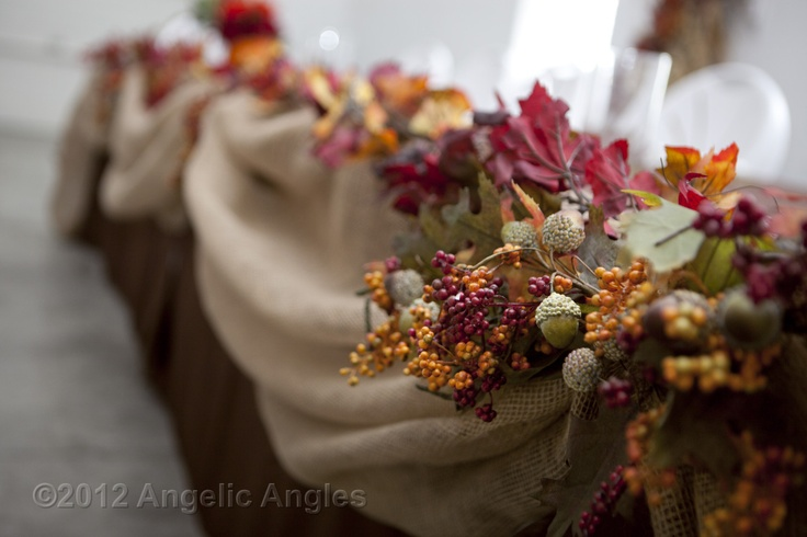 Head table  brown tablecloths, white isicle lights  underneath and burlap swag