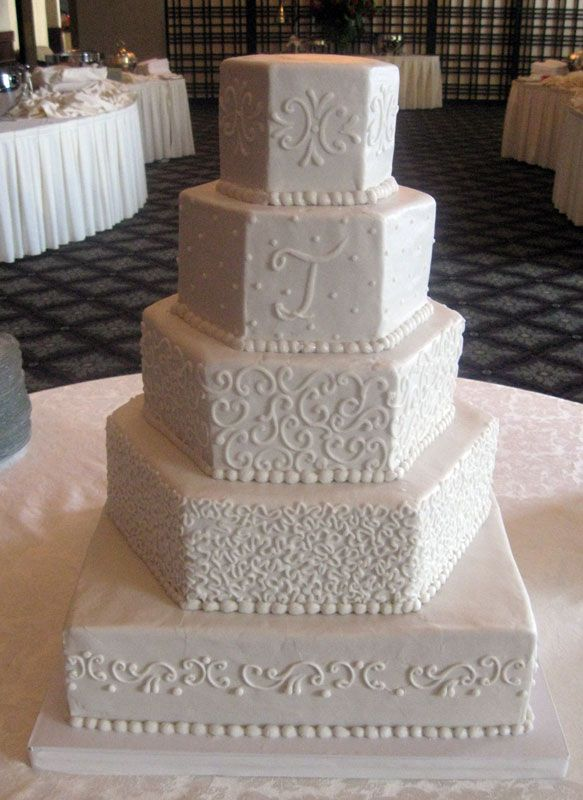 Want an all white, hexagon-tiered cake with monogram. This is getting close.