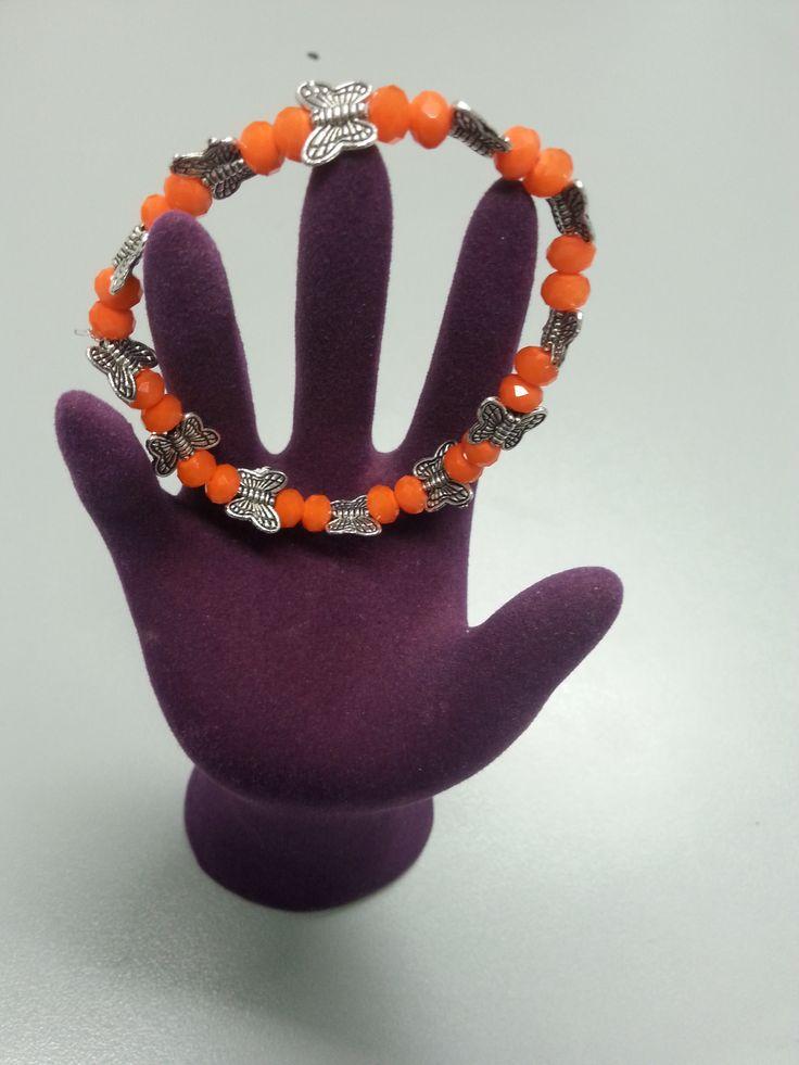 Pulsera de bolas naranjas con pequeñas mariposas de plata entre medias. Perfecta para cualquier ocasión.