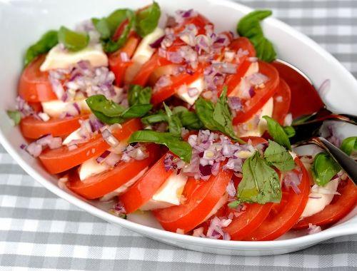 Tomat och mozzarellasallad. Skivade tomater varvat med skivad mozzarellaost med finhackad rödlök, basilika, vinäger samt olivoja, salt och peppar är en mycket god och