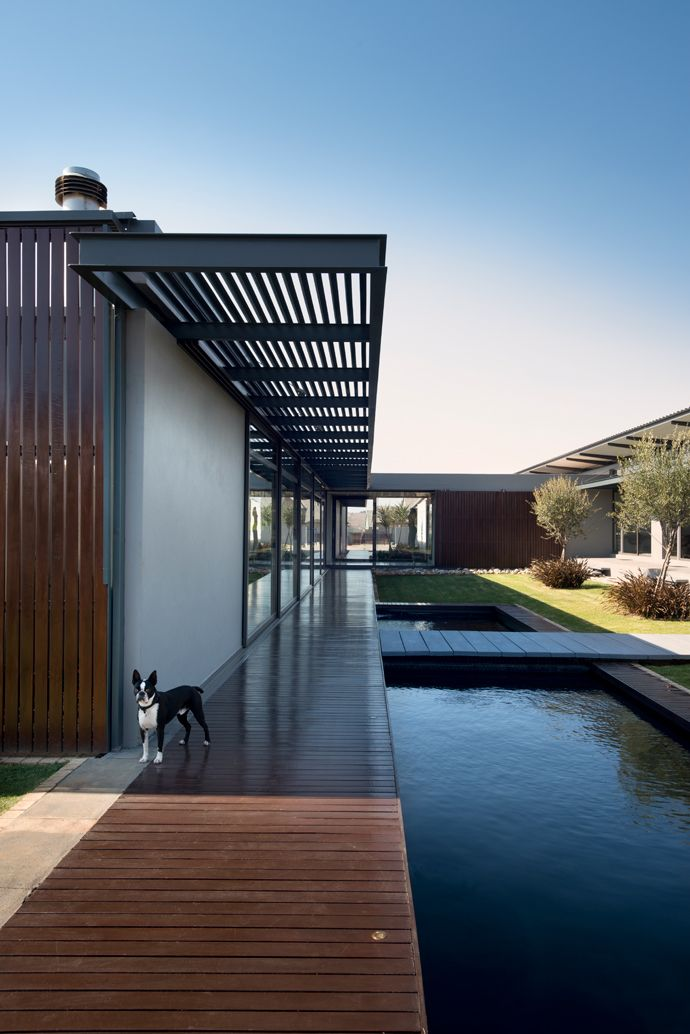 Teak accents soften the high-tech steel and glass exterior finishes. Running parallel to the inner courtyard, the teak walkway forms a central axis that runs the entire length of the house to connect all the living spaces.