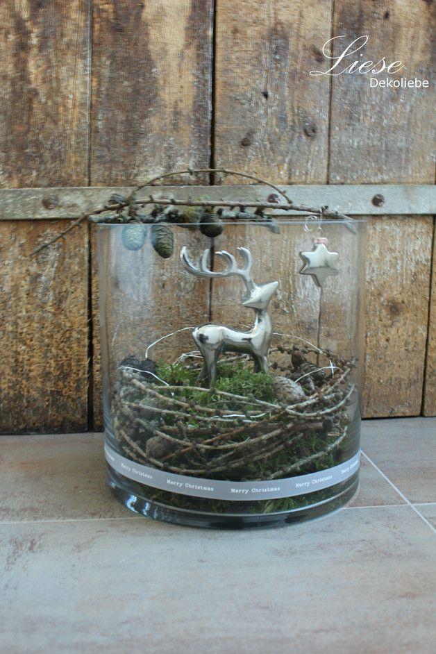 *Großes Windlichtglas wunderhübsch auf die kommende Jahreszeit ausdekoriert. Das silberfarbene Reh steht im Moosbett, umringt von Lärchenzweigen und einer Lichterkette, und schaut nach den...