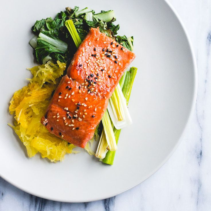 This sheet-pan dinner star is wild caught salmon in a sesame oil glaze, baked on top of leeks, bok choy & spaghetti squash. gluten-free, dairy-free meal.