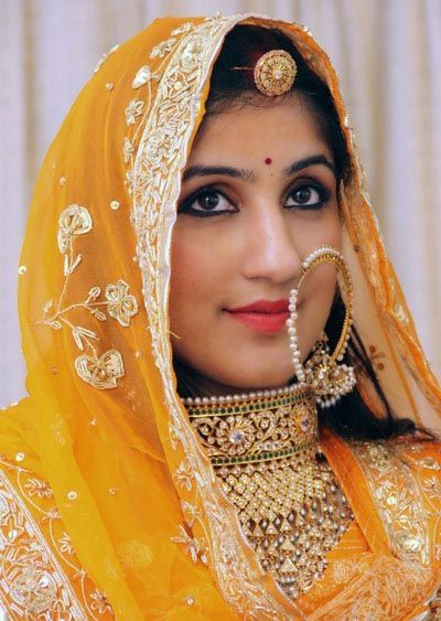 North Indian bride with heavy gold necklace,pearls nath and bhor/mangtika