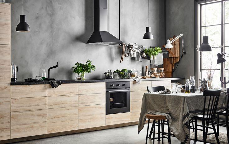Cucina lineare con ante frassino con lo sfondo di una parete grigia effetto cemento e un tavolo da pranzo con una tovaglia in lino - IKEA
