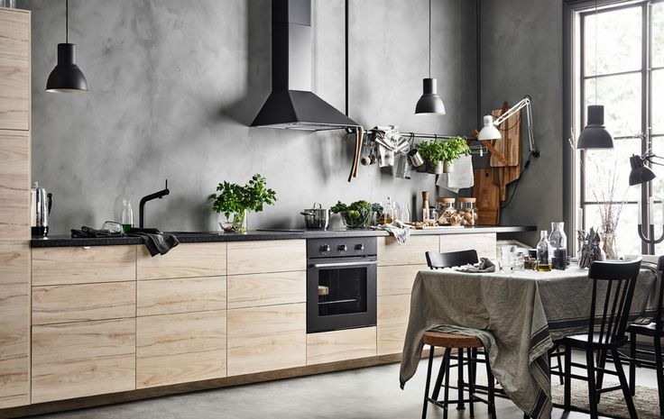 A straight-line kitchen with a row of base cabinets with ash fronts against a gray, concrete looking wall  and a dinng table with a linen table cloth
