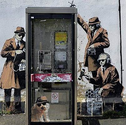 A mural by the elusive artist Banksy of 1950s-style spies (and Tali) huddled around a payphone box, appeared on the side of a house in Cheltenham in April 2014.