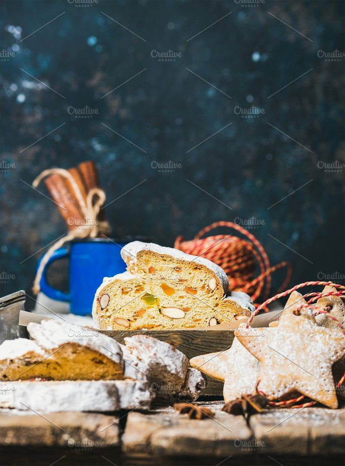 #Christmas cake Stollen  Piece of Traditional German Christmas cake Stollen with festive gingerbread star shaped cookies selective focus dark blue grunge background copy space vertical composition