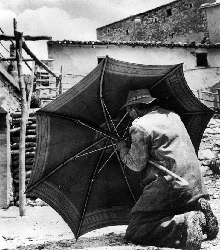 Campi di Norcia, anni 40. Un anziano pastore intento a riparare il suo ombrello. Tanti chiodi sulle suoole delle sue scarpe, che, come il suo ombrello, dovevano durare molti anni.