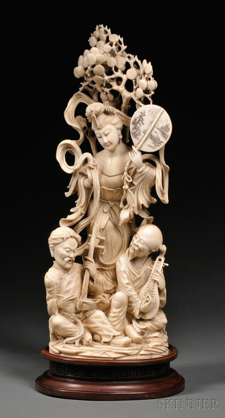 Ivory Group, China, standing figure of courtesan holding a fan and ribbons with two seated musicians at her feet and pine tree at her back, with stand, ht. 16 in