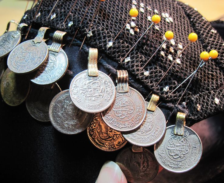"""Quickly stitch on a row of coins to a bra.  Coins with loop tops, can be strung onto a cord.  Distribute the coins using pins to space them to your taste.  Then hand sew the cord to the bra, being sure to make loops on either side of each coin to prevent them from sliding out of place.  This method will be in my upcoming book """"The Cloth of Egypt: All About Assiut"""" with detail photos and descriptions.  By Dawn Devine ~ Davina -  www.davina.us"""