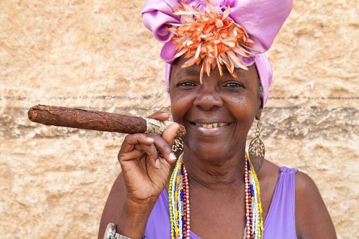 cuban dresses for women | woman in colourful Cuban clothing endulges on a world-renowned Cigar ...