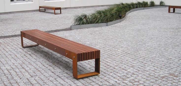 """Straight bench with a solid wood slatted seat, closed with suitable round nylon elements, with a special single-post steel support in a double """"T"""" or """"L"""" shape. It can be accessorised with a solid wood backrest."""