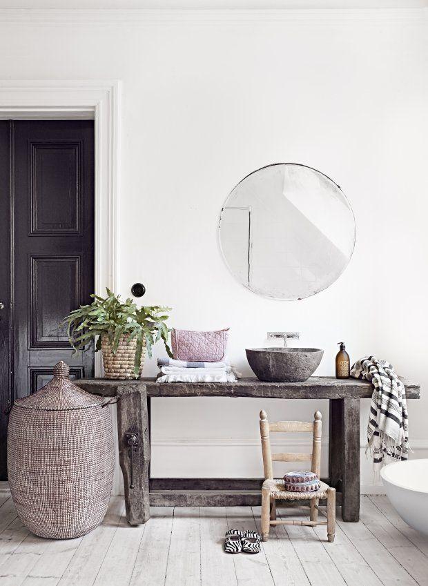 #reforma #baño con lavabo de piedra sobre mesa reutilizada, espejo circular, suelo parqué.
