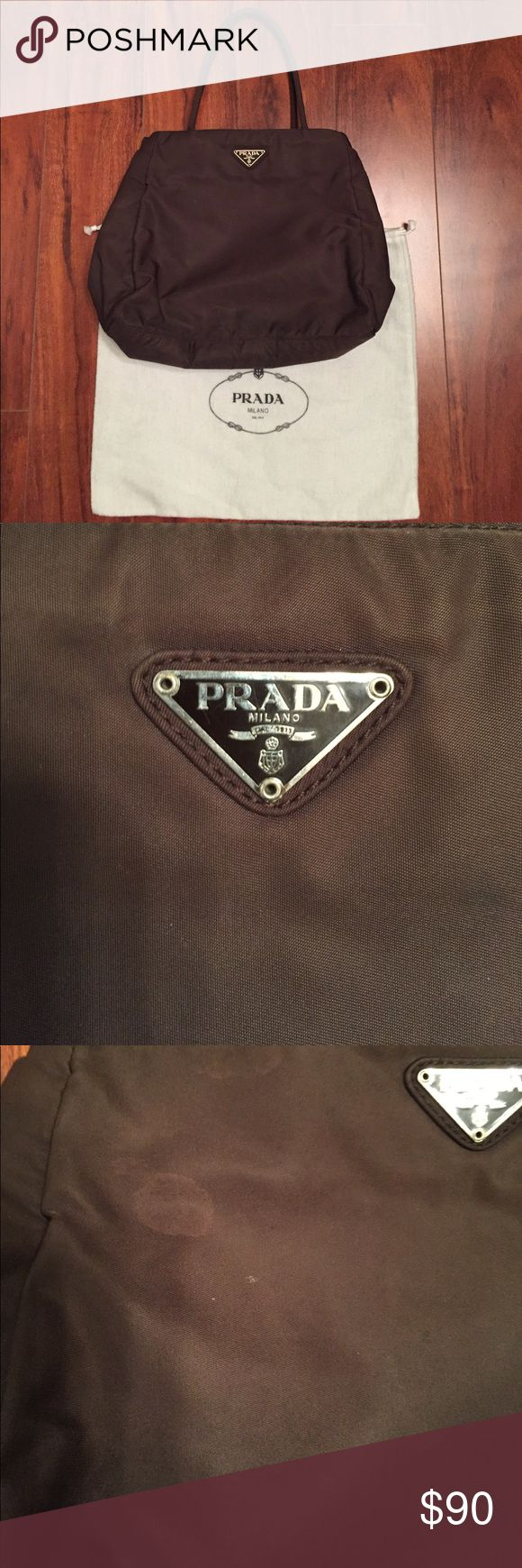 Authentic Prada Tessuto tote This purse shows wearing and aging signs. Stains on the fabric. You can clean it professionally. Price reflects this. Inside is clean. No rips or odor. Still has a lot of life. Comes with dust bag but no authenticity card. Prada Bags Totes