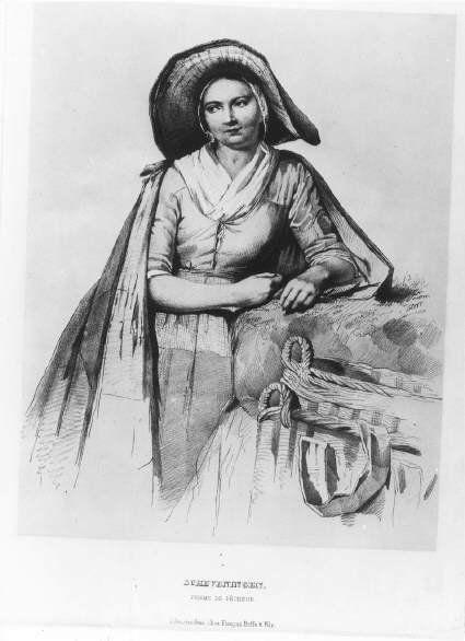 Negentiende-eeuwse Scheveningse vissersvrouw. Ze draagt een mutsje met een gevoerde, rieten vishoed. Zij is gekleed in een borstrok en een een effen jakje met haken en ogen, met een witte halsdoek erin. De schoudermantel is gevoerd. De blauwe schort heeft een bovenstuk van dobbelsteen. Ze leunt op een muur. Naast haar een mand. 1830 AWM Mensing (uitgever Francois Buffa en Zonen); lithografie #ZuidHolland #Scheveningen