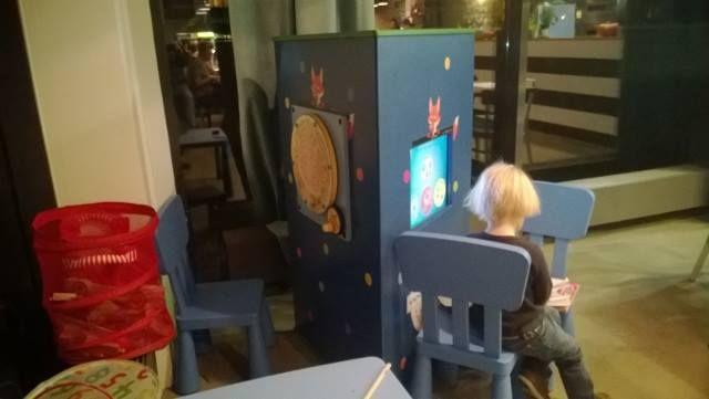 Interaktywny kącik dla dzieci - trójścienna wieża Foxbox w restauracji włoskiej. Na pozostałych ścianach gry manualne -  labirynty, przemieszczanie kulek...