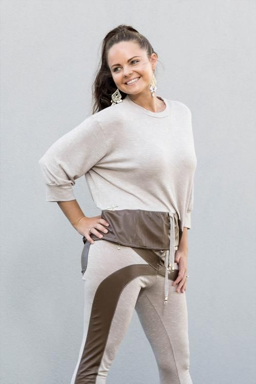 Coco Leather 3/4 Sleeve Top - This super soft, stretch, active leisure wear top is simple and funky; true comfort with an edge. It features, 3/4 sleeves,round top stitched neckline and a coco coloured leather peplin that is concaved around the waistline. It also has a drawstring tie in the front.