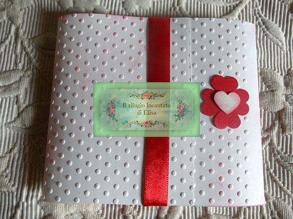 Partecipazione bianca per matrimonio realizzata a mano con fiocco rosso e cuore. Handmade white and red wedding invitation.