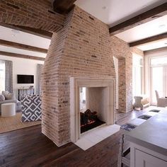 Transitional kitchen features a brick two sided fireplace with see through firebox with view to living room. Description from decorpad.com. I searched for this on bing.com/images
