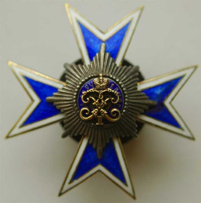 Russian Imperial Badge of the Iife-Guards Cuirassier Regiment of Her Majesty The Empress Maria Feodorovna. Gold Maltese cross covered in light blue enamel with narrow white borders. In the centre of the cross is the silver St. Andrew's star. In the central medallion of the star is the gold cypher of the Emperor Peter I beneath the gold Imperial crown.