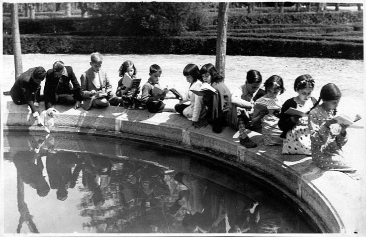 Título:    Niños leyendo en la biblioteca del parterre del Retiro  Fecha:    1936  Descripción:    Fotografía extraída del Album de recortes de la Biblioteca Musical